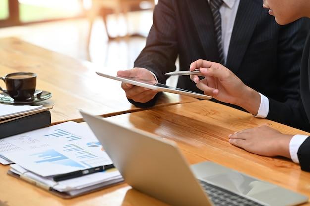 Geschäft beraten sich, der geschäftsmann, der mit finanzdokument und tablette mit sitzung und planung arbeitet. Premium Fotos
