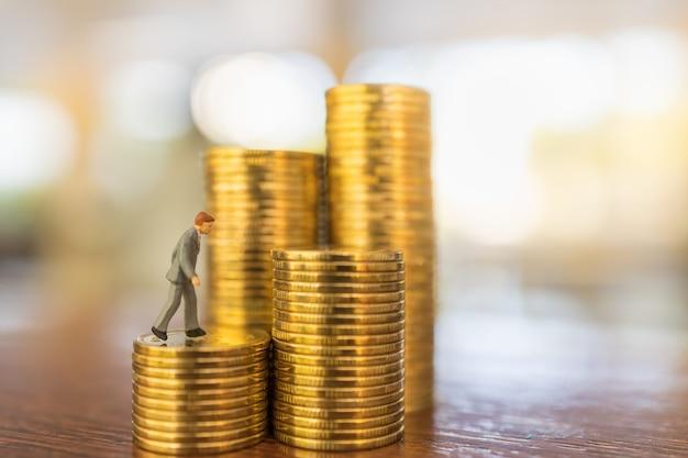 Geschäfts-, geldinvestitions- und planungskonzept. schließen sie oben von geschäftsmann-miniaturmenschenfigur, die oben auf stapel von goldmünzen auf holztisch mit kopie sapce geht. Premium Fotos