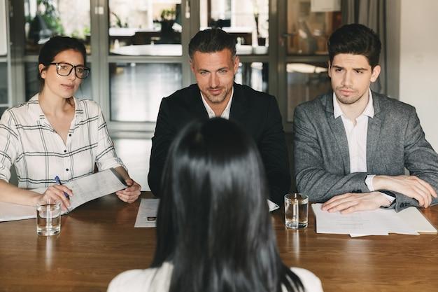 Geschäfts-, karriere- und rekrutierungskonzept - gruppe von arbeitgebern in abendgarderobe, die im büro am tisch sitzen und eine frau für einen job in einem großen unternehmen interviewen Premium Fotos