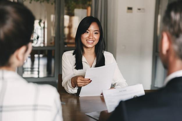 Geschäfts-, karriere- und rekrutierungskonzept - junge asiatische frau, die lächelt und lebenslauf hält, während interview als kandidat für job in großem unternehmen Premium Fotos