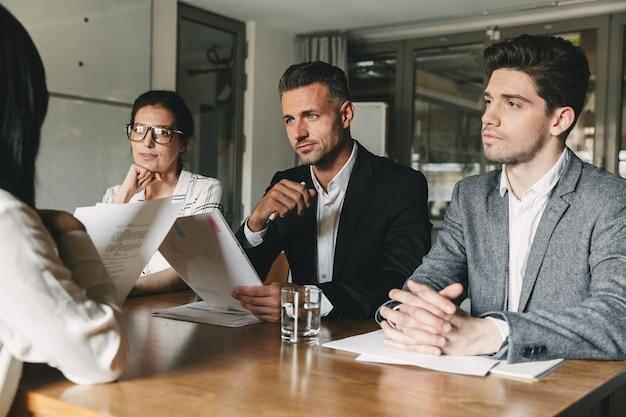 Geschäfts-, karriere- und vermittlungskonzept - ausschuss von geschäftsleuten, die im büro am tisch sitzen und die frau während des treffens interviewen Premium Fotos