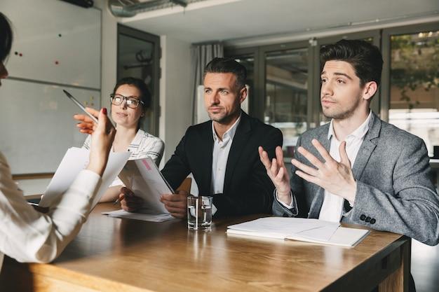 Geschäfts-, karriere- und vermittlungskonzept - drei geschäftsführer oder geschäftsführer, die im büro am tisch sitzen und während des interviews mit neuen mitarbeitern verhandeln Premium Fotos