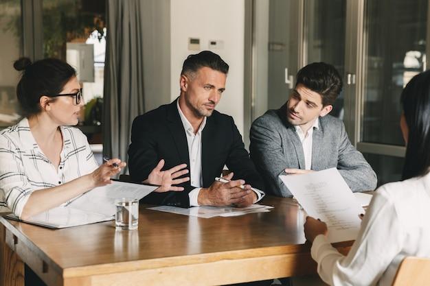 Geschäfts-, karriere- und vermittlungskonzept - drei geschäftsführer oder geschäftsführer sitzen im büro am tisch und besprechen die arbeit mit neuen mitarbeitern während des interviews Premium Fotos