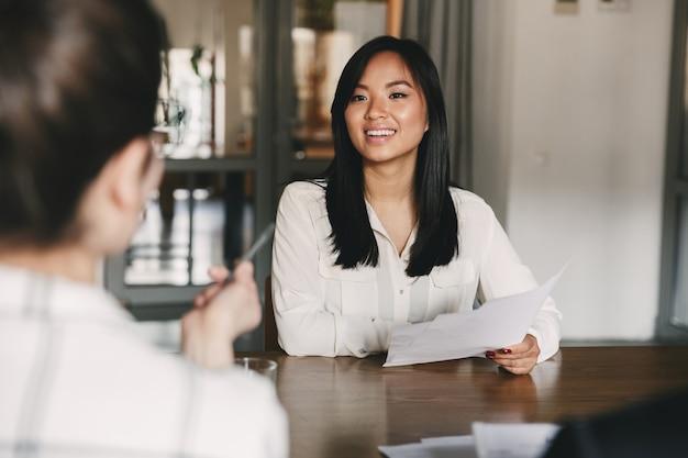 Geschäfts-, karriere- und vermittlungskonzept - freudige asiatische frau, die lächelt und lebenslauf hält, während sie während des firmenmeetings oder des vorstellungsgesprächs vor direktoren sitzt Premium Fotos