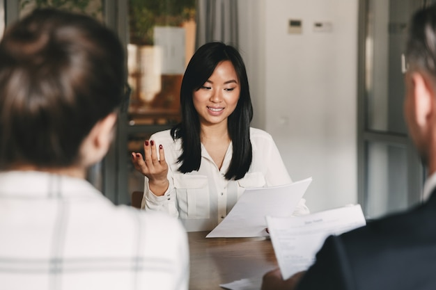Geschäfts-, karriere- und vermittlungskonzept - geschäftsmäßige asiatische frau, die einen lebenslauf hält und mit arbeitgebern eines großen unternehmens während eines unternehmenstreffens oder eines vorstellungsgesprächs spricht Premium Fotos