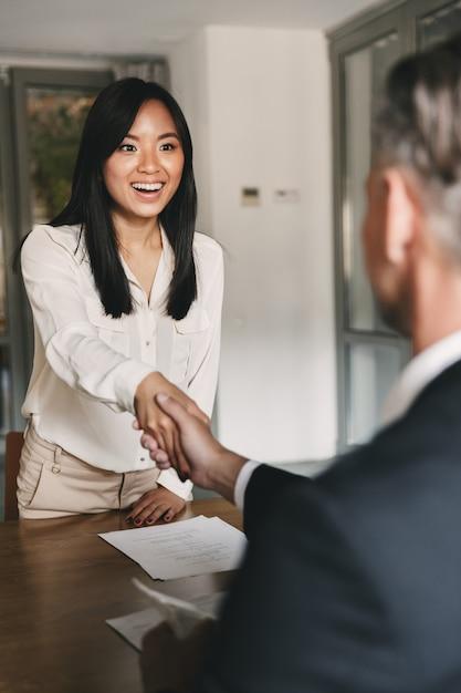 Geschäfts-, karriere- und vermittlungskonzept - glückliches händeschütteln der asiatischen frau mit dem männlichen geschäftsführer oder arbeitgeber eines großen unternehmens nach erfolgreichen verhandlungen oder interviews Premium Fotos