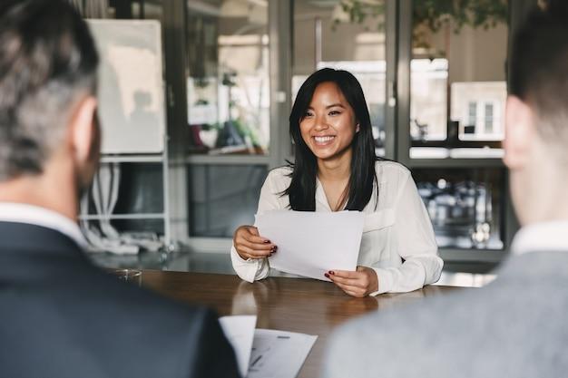 Geschäfts-, karriere- und vermittlungskonzept - junge asiatische frau, die lächelt und lebenslauf hält, während sie während des firmenmeetings oder des vorstellungsgesprächs vor direktoren sitzt Premium Fotos