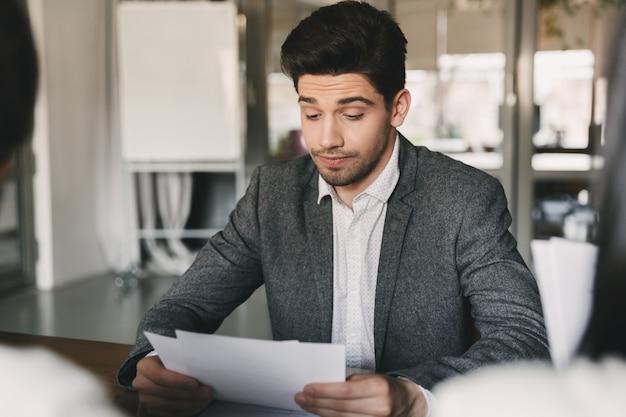 Geschäfts-, karriere- und vermittlungskonzept - kaukasischer mann der 30er jahre, der seinen lebenslauf oder seine dokumente während eines vorstellungsgesprächs im amt mit einem ausschuss geschäftsmäßiger personen liest Premium Fotos