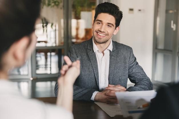 Geschäfts-, karriere- und vermittlungskonzept - lächelnder kaukasischer mann der 30er jahre, der mit dem ausschuss der geschäftsmäßigen leute während des vorstellungsgesprächs im amt verhandelt Premium Fotos