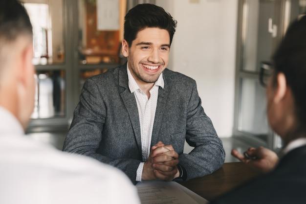 Geschäfts-, karriere- und vermittlungskonzept - lächelnder kaukasischer mann der 30er jahre verhandelt mit mitarbeitern eines großen unternehmens während eines vorstellungsgesprächs im büro Premium Fotos