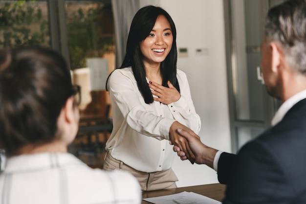 Geschäfts-, karriere- und vermittlungskonzept - zwei geschäftspartner im büro, die einer jungen asiatischen frau nach erfolgreichen verhandlungen oder interviews die hand schütteln Premium Fotos