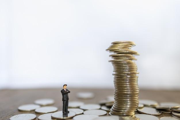 Geschäfts-, risiko-, investitions- und sparkonzept. schließen sie oben von geschäftsmann-miniaturmenschen, die stehen und zu instabilem stapel von münzen mit kopienraum suchen. Premium Fotos