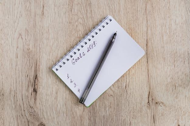 Geschäfts- und bürokonzept - leeres notizbuch und schwarzer stift auf holztisch. ziele 2019. minimale flachlage, draufsicht. Premium Fotos