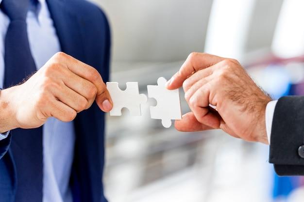 Geschäfts- und teamwork-konzept; geschäftshände, die puzzleteil zusammenfügen. Premium Fotos