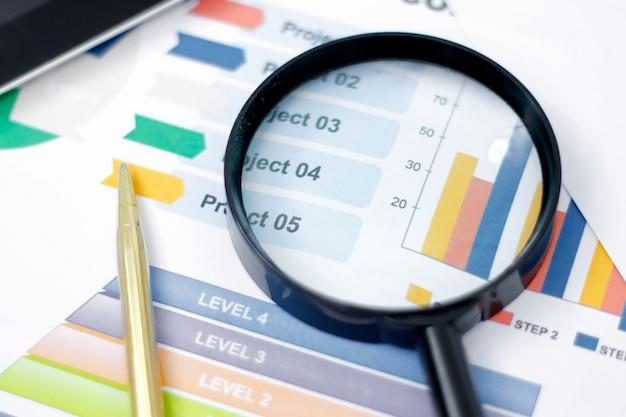 Geschäftsanalysen und statistiken. analysieren von einkommensdiagrammen und -diagrammen und von lupe auf tabelle Premium Fotos