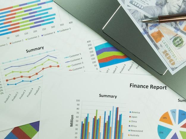 Geschäftsberichtdiagramm und finanzdiagrammanalyse mit dollargeld und stift auf dem tisch Premium Fotos