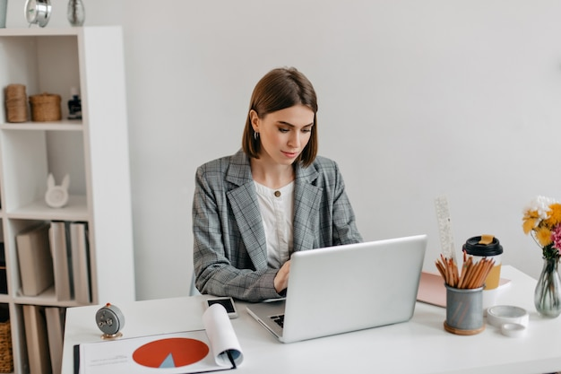 Geschäftsdame in der grauen jacke, die im laptop arbeitet. porträt der frau im amt. Kostenlose Fotos