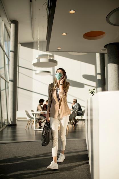 Geschäftsfrau am handy, die im büro geht und maske als virenschutz trägt Premium Fotos
