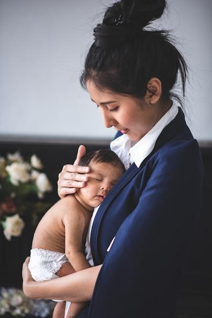 Geschäftsfrau arbeitet, indem sie ihr baby hält Premium Fotos