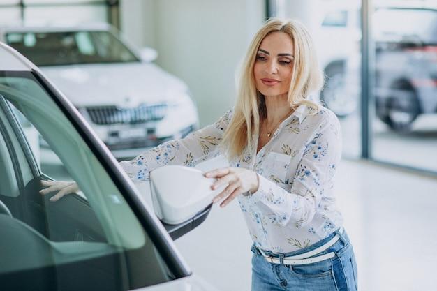 Geschäftsfrau auf der suche nach einem auto-handy in einem autohaus Kostenlose Fotos