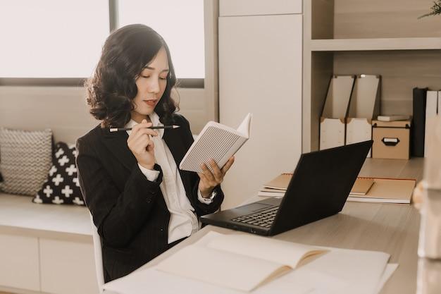 Geschäftsfrau denken, um etwas auf das notizbuch zu schreiben. Premium Fotos