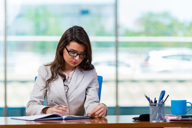 Geschäftsfrau, die am schreibtisch sitzt Premium Fotos