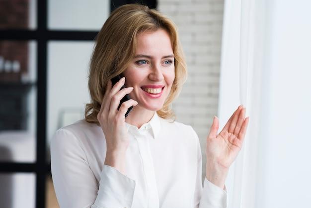 Geschäftsfrau, die am telefon und dem lächeln spricht Kostenlose Fotos