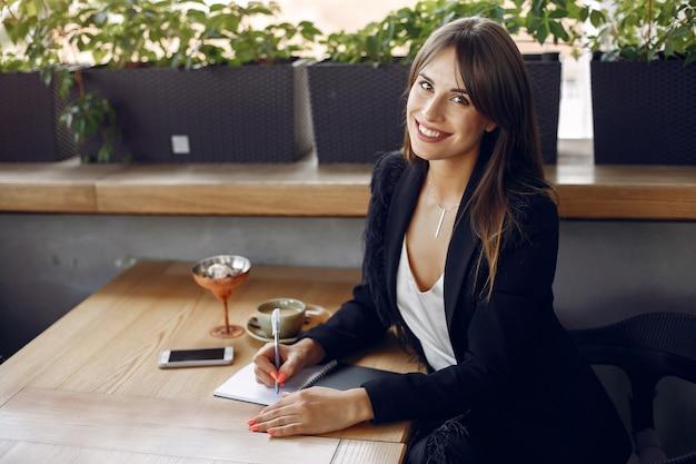 Geschäftsfrau, die am tisch in einem café und in einem arbeiten sitzt Kostenlose Fotos