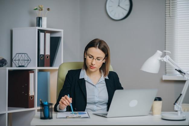 Geschäftsfrau, die an einem laptop in ihrem modernen büro-haltepapier-finanzbericht arbeitet. Premium Fotos