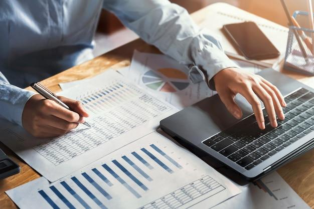 Geschäftsfrau, die an schreibtisch unter verwendung des laptops für kontrolldaten der finanzierung im büro arbeitet Premium Fotos