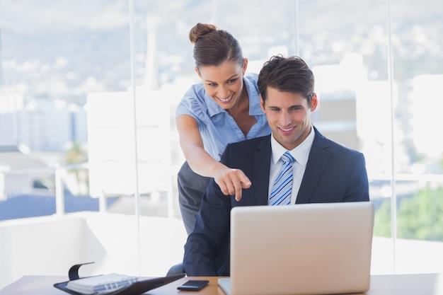 Geschäftsfrau, die auf den laptop zeigt und im büro lächelt Premium Fotos