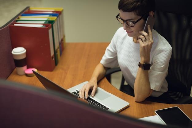 Geschäftsfrau, die auf handy spricht, während laptop im büro verwendet wird Kostenlose Fotos