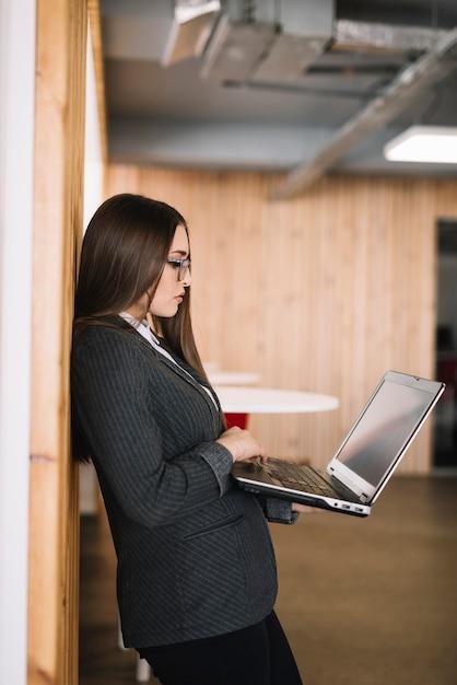 Geschäftsfrau, die auf laptoptastatur an der wand schreibt Kostenlose Fotos