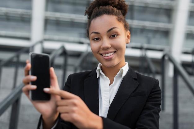 Geschäftsfrau, die auf telefon zeigt Kostenlose Fotos