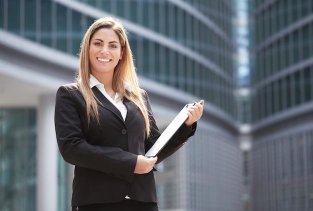 Geschäftsfrau, die außerhalb des bürogebäudes arbeitet Premium Fotos