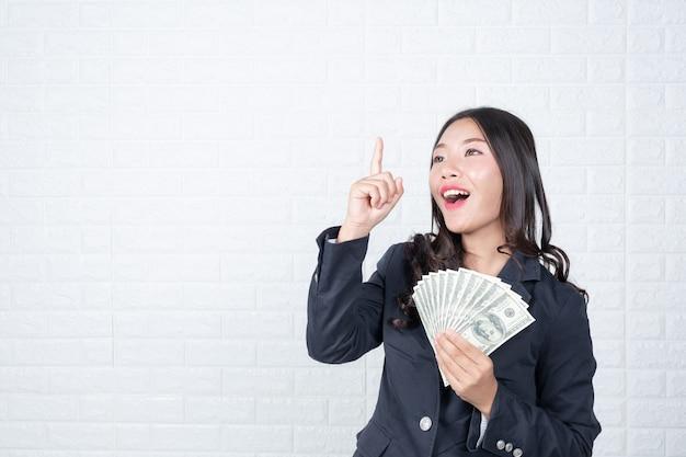 Geschäftsfrau, die banknote, bargeld separat hält, weiße backsteinmauer machte gesten mit gebärdensprache. Kostenlose Fotos