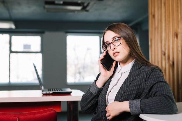 Geschäftsfrau, die bei tisch telefonisch spricht Kostenlose Fotos