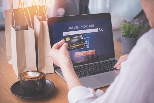 Geschäftsfrau, die den laptop zahlt kreditwarenkorb, konzept des einkaufens online verwendet. Premium Fotos