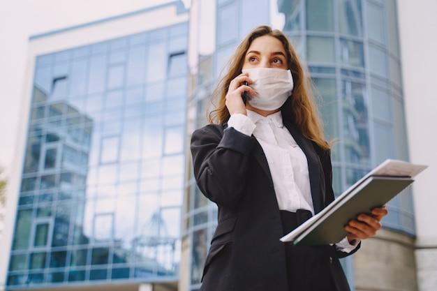 Geschäftsfrau, die draußen im bürogebäude der stadt steht Kostenlose Fotos