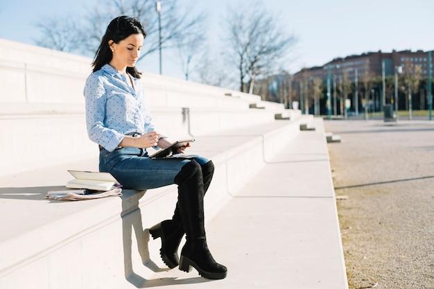 Geschäftsfrau, die draußen mit tablette arbeitet Kostenlose Fotos
