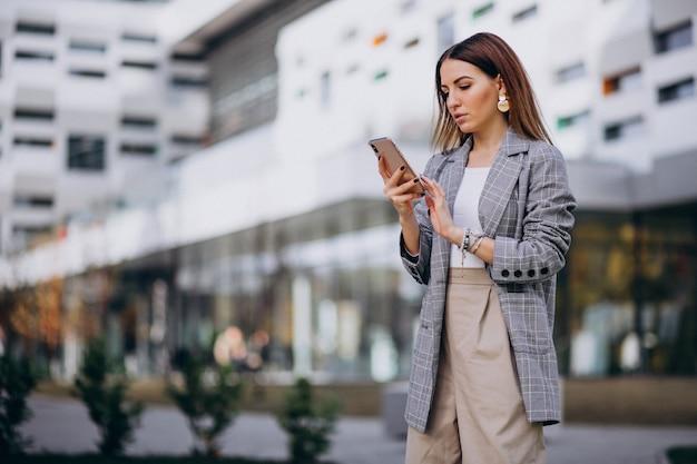 Geschäftsfrau, die draußen telefon in der straße durch das gebäude verwendet Kostenlose Fotos