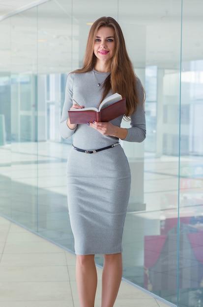 Geschäftsfrau, die ein tagebuch in ihren händen hält und die kamera betrachtet Premium Fotos