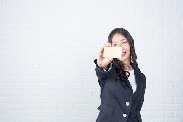 Geschäftsfrau, die eine unterschiedliche geldautomatenkarte, weiße backsteinmauer hält machte gesten mit gebärdensprache. Kostenlose Fotos
