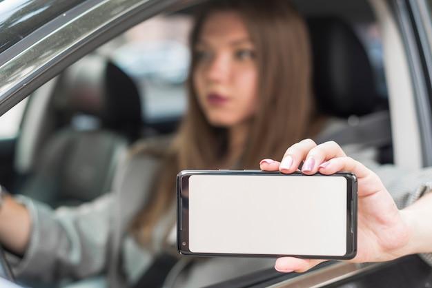 Geschäftsfrau, die einen smartphone im auto zeigt Kostenlose Fotos