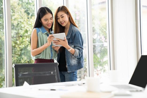 Geschäftsfrau, die finanzzahlen auf einer digitalen tablette bearbeitet und analysiert Premium Fotos