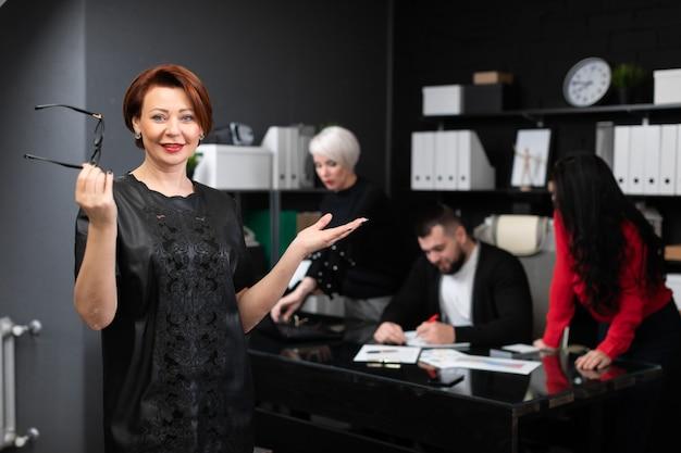 Geschäftsfrau, die gläser an von den büroangestellten besprechen projekt hält Premium Fotos