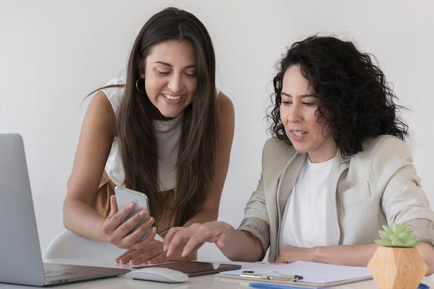 Geschäftsfrau, die ihrem kollegen etwas am telefon zeigt Kostenlose Fotos