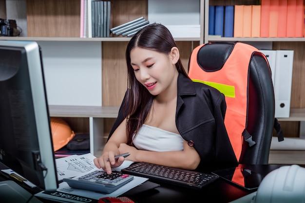 Geschäftsfrau, die im büro mit einem lächeln beim sitzen arbeitet. Kostenlose Fotos