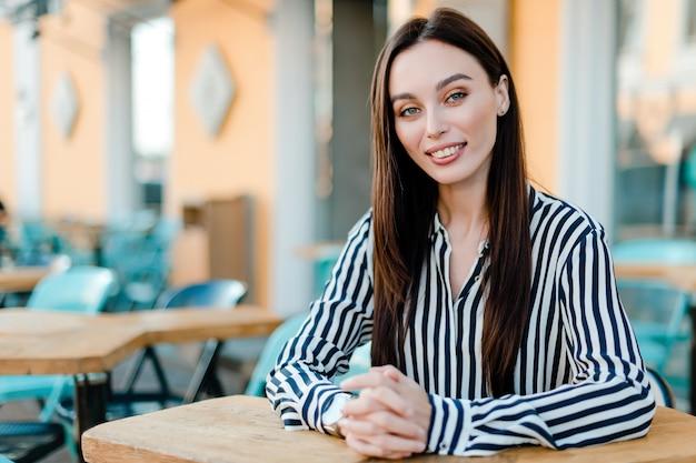 Geschäftsfrau, die im café und im lächeln sitzt Premium Fotos