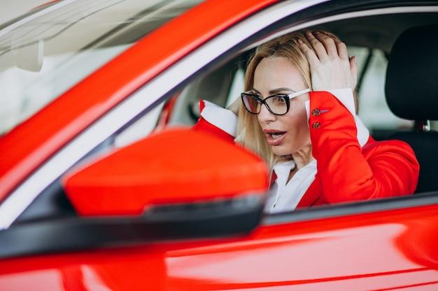Geschäftsfrau, die in einem neuen auto in einem autoausstellungsraum sitzt Kostenlose Fotos